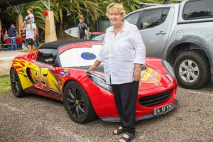 Sandra standing in front of a Lotus sports car who suffers from a rare chronic disorder